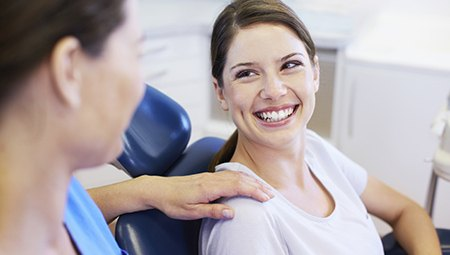 Woman in dental chair smiling up at dentist